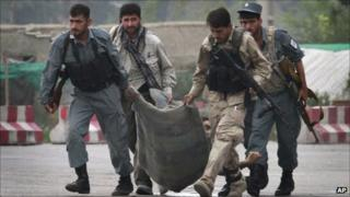 Afghan security forces carry the body of a colleague, who was killed during a gun battle with Taliban militants in Kabul, Afghanistan on Wednesday Sept. 14,2011