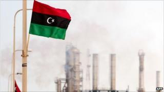 The new Libyan flag flutters outside an oil refinery in Zawiya on 23 September 2011