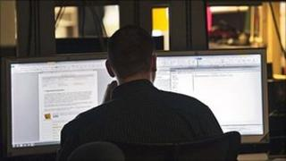 Generic image of man reading from computer screens