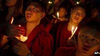 Exiled Tibetan monks hold a candlelight vigil in Dharamsala, India, as they react to reports that two Tibetan monks at the Kirti Monastery in Sichuan province set themselves on fire on 26 September