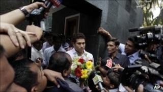 Sachin Tendulkar receives flowers from school children after moving in