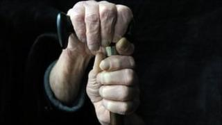 Pensioner with hands on stick