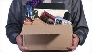 Man in suit carrying a box