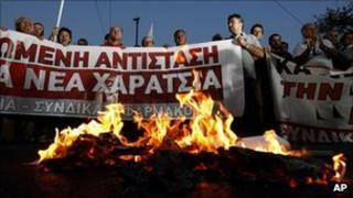 Greek demonstrators burn copies of emergency tax notices