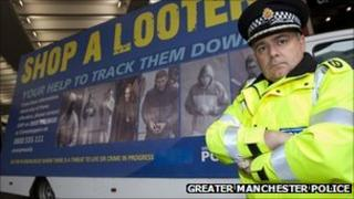 Policeman stood by a 'Shop a Looter' billboard