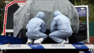 Police forensic officers examining a car