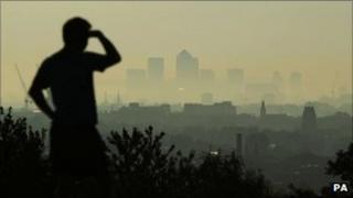 A man looks through the early morning haze across to Canary Wharf