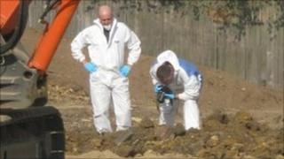 Two men, one with a camera, overlooking the site where skeletal remains were found on Valley Road, Ipswich