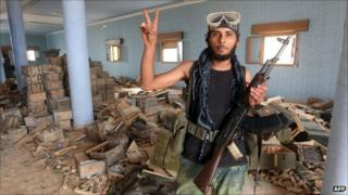A Libyan National Transitional Council fighter flashes the victory sign after finding a weapons depot inside a house in the village of Qasr Abu Hadi, Gaddafi's birthplace.