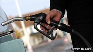 Man holding nozzle of petrol pump