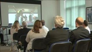 Students and guests view the charity's promotional video.