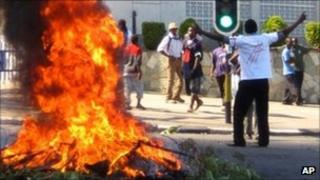 A protester burns vegetation in a street in Lilongwe, Malawi, as anti-government demonstrations swept across the country amid worsening economic conditions - 20 July 2011