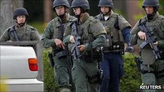 Security personnel perform yard-to-yard searches during a manhunt in Sunnyvale, California, 5 October 2011.