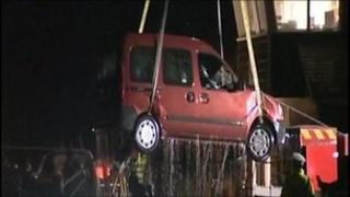 Car being lifted out of river
