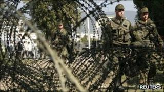 German peacekeeping troops walk beside a barricade on the main bridge in the divided Kosovan town of Mitrovica, 5 October