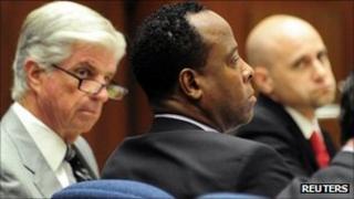 Dr Conrad Murray defence attorneys J. Michael Flanagan and Nareg Gourjian look at him during his trial, Los Angeles 12 October 2011.