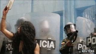 A student protester confronts riot police during a demonstration in Bogota, 12 October 2011