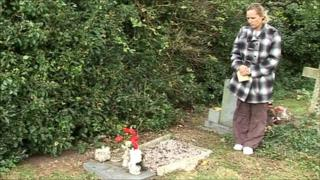 Michelle Holness standing beside her dead son's grave