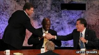 Rick Perry, Herman Cain and Mitt Romney at a Republican debate, 11 October 2011