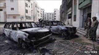 Anti-Gaddafi fighters stand near burnt cars in Sirte. Photo: 18 October 2011
