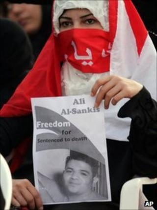 A Bahraini anti-government protester holds a banner calling for the freedom of Ali Al-Sankis, who has been sentenced to death for killing a police officer, 30 September 2011