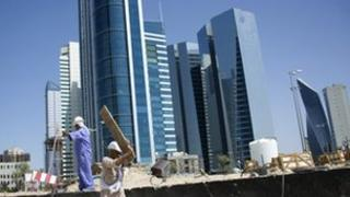 Foreign construction workers are seen on a building site in Kuwait City