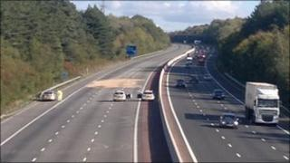 Highways Agency workers on the closed northbound section of the M3 after the fuel spillage