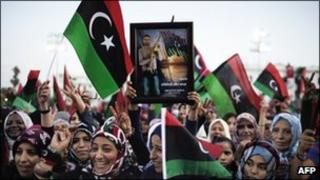 """Libya women wave their new flag during celebrations in the streets of Tripoli following news of Moamer Kahdafi""""s capture and death"""