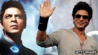 Shah Rukh Khan poses in front of a poster for his film Ra.One