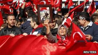 Demonstrators shout slogans and wave Turkey's national flag during a protest against the latest attacks against the Turkish military in central Ankara on Thursday