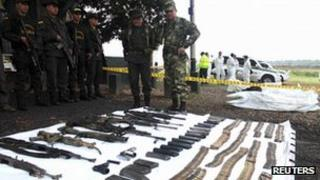 Policemen and soldiers look at rifles, mortars and grenade launchers seized from Farc guerrillas in Cucuta on 11 October 2011.