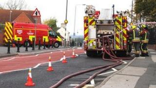 Firefighters stand next to a fire engine in Selston, Nottinghamshire