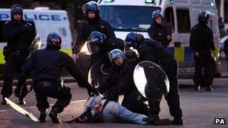 Police detain a man during rioting in Birmingham