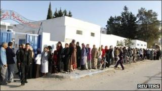 Citizens wait in line to cast their ballots at a polling station during an election in Tunis
