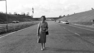 "Prime Minister Margaret Thatcher stands on an empty stretch of motorway in 1986 on the day she opened the ""missing link"" at Radlett, Hertfordshire."