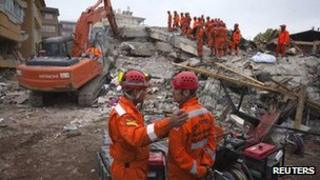 Two members of a Turkish search and rescue team talk to each other as others search a collapsed building for earthquake survivors in Ercis
