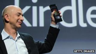 Amazon's chief executive, Jeff Bezos, holds up the Kindle Fire tablet