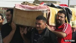 Residents carry a coffin for a victim of the bombing in the Ur district of Baghdad