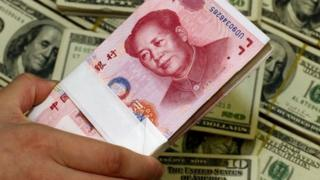 Chinese yuan next to the US currency