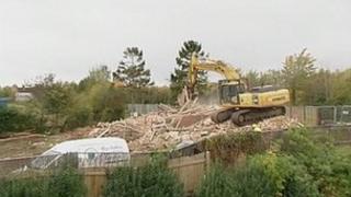 A bulldozer complete the demolition work