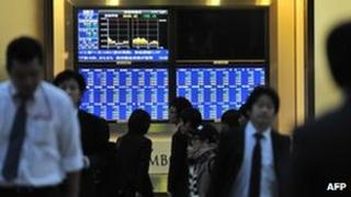 Pedestrians walk past an electronic share price board