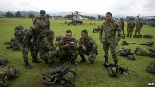 Colombian soldiers who took part in the raid against Alfonso Cano listen to news at a military base in Popayan