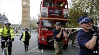 A team of 10 police officers and 10 members of the Armed Forces pull a fully laden double-decker bus for one mile