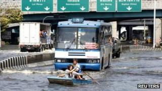 Residents in a boat row along a Bangkok street as a bus follows through the flood waters on 7 November 2011