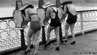 Holidaymakers back in 1935 look at picture peep shows on the pier at Llandudno