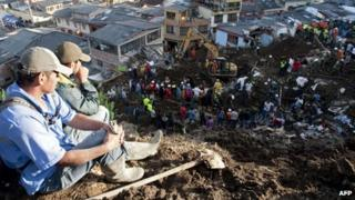 Two men observe the rescue works in Manizales after a landslide struck on Saturday