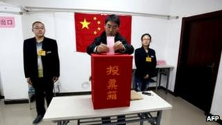A Chinese man casts his vote during the local people's congress election in Beijing, 8 November 2011