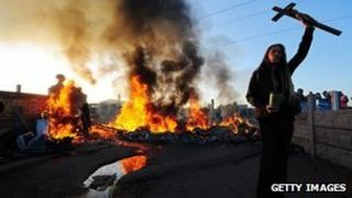 A traveller holds aloft a crucifix as a caravan burns on Dale Farm, near Basildon, east of London, on October 19, 2011