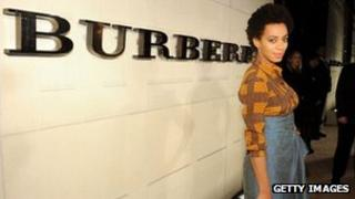 A model wearing Burberry clothes in front of their sign