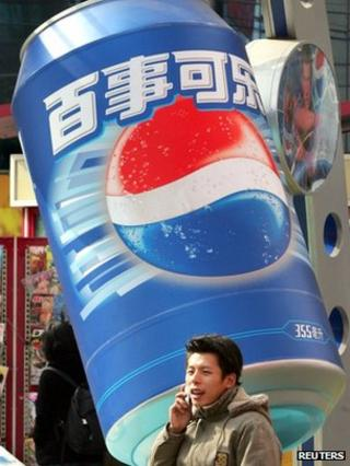 A Chinese shopper talks on his phone as he walks past a Pepsi advertisement in Shanghai (file photo)